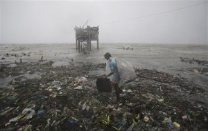 A Filipino man scavenges recyclable materials near a house on stilts stands by the bay as strong winds and rains caused by Typhoon Koppu hit the coastal town of Navotas, north of Manila, Philippines Sunday, Oct. 18, 2015. The slow-moving typhoon blew ashore with fierce wind in the northeastern Philippines early Sunday, toppling trees and knocking out power and communications. (AP Photo/Aaron Favila)