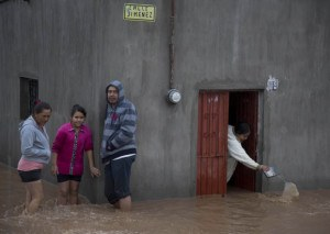 Residents outside a flooded house 150 km northwest of Guadalajara. Hurricane Patricia made landfall on a sparsely populated stretch of Mexico's Pacific coast as a Cat. 5, avoiding direct hits on Puerto Vallarta and the major port city of Manzanillo  (AP Photo/Eduardo Verdugo)