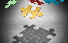 Putting the puzzle together teamwork concept as a business success symbol with four divided pieces of a jigsaw puzzle flying in the air creating a cast shadow that unifies the team as a unity metaphor. 3D