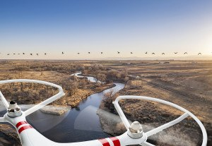 A small quadcopter drone flying over river landscape with Canadi