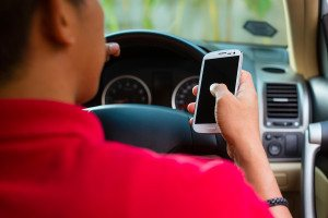 Asian man sitting in car with mobile phone in hand texting while