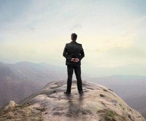 Businessman standing on a peak