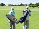 Golfer friends walking and holding their golf bags on a sunny da