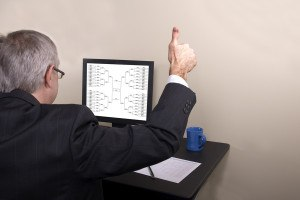 A businessman giving thumbs up looking at his March Madness bracket