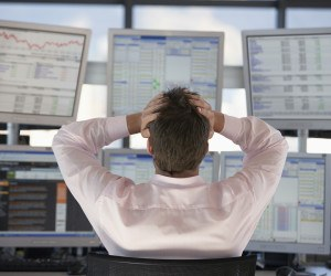 Rear view of stock trader with hands on head looking at multiple- confused investor