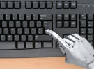 Robot hand typing on a computer keyboard.