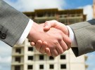 Photo of handshake of business partners after striking deal on background of building under construction