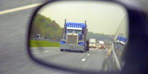 Large truck traveling down a highway as seen through a side view mirror