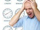 caucasian man stressed by jet lag with time zone clock backgroun