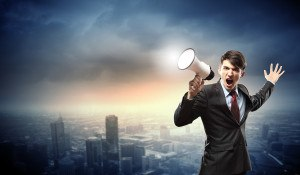 young businessman in black suit screaming into megaphone